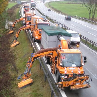 Drei Mähfahrzeuge mähen hinter der Autobahn-Leitplanke